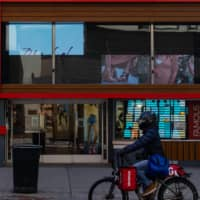 A Grubhub delivery worker passes by a Famous Footwear store in New York's Herald Square area on May 12. | BLOOMBERG