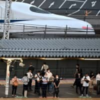 People wearing face masks wait for local trains while a Shinkansen passes JR Shimbashi Station in Tokyo on Wednesday. | AFP-JIJI