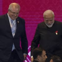 Australian Prime Minister Scott Morrison and Indian Prime Minister Narendra Modi walk together after posing for a group photo during the East Asia Summit in Nonthaburi, Thailand, in November last year. | AP