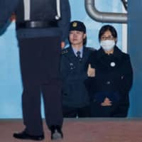 Choi Soon-sil, confidante of South Korea's former President Park Geun-hye, is escorted to a prison bus at the Seoul Central District Court in February 2018.  | BLOOMBERG