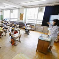 An elementary school in Tokyo's Katsuhika Ward implements social distancing measures in a classroom on June 1. | KYODO