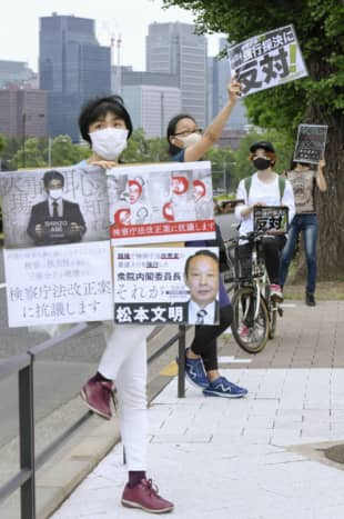 People stand in front of the parliament building in Tokyo on May 15 to protest a bill pushed by the ruling coalition that would extend the retirement age for prosecutors. | KYODO