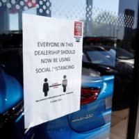 A social distancing sign is seen at a Nissan car dealership in Northwich, England, last month. | REUTERS