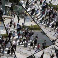 Pedestrians are reflected in the mirrored ceiling of a shopping mall in Tokyo on Thursday. The hiring rate for those who graduated from university this spring stood at 98 percent as of April 1, according to labor ministry data. | AP
