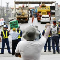 Protesters rally Friday in front of the gates of the U.S. Marines Corps Camp Schwab, adjacent to a site in the Henoko coastal area in Nago, Okinawa Prefecture, where reclamation work has resumed. | KYODO