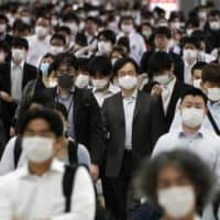 People commute in Tokyo on June 5. Researchers have found that death rates were lower in countries like Japan that have a combination of high government efficiency and high cultural 'tightness' — strong norms and a pressure for conformance. | AP
