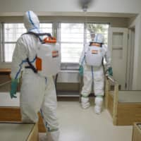 Officers disinfect a cell at Kyoto Prison on Friday as part of a drill to prepare for a possible COVID-19 outbreak at a jail facility. | KYODO