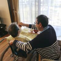 A 44-year-old man employed by a nursing care home in Natori, Miyagi Prefecture, attends to a resident in March 2018.  | KYODO