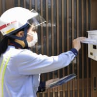 A postal delivery worker puts masks procured by the government into a mailbox in Nagoya, Aichi Prefecture, in May.   | KYODO