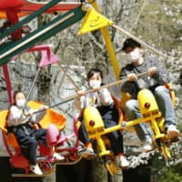Visitors enjoys a ride at the Toshimaen amusement park in Tokyo on March 21. | KYODO
