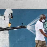 A man walks next to graffiti depicting a cleaner wearing protective gear spraying viruses with the face of Brazilian President Jair Bolsonaro amid the coronavirus pandemic in Rio de Janeiro on Friday. | REUTERS