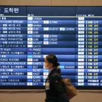 An international arrival information board at Tokyo's Haneda Airport showing a large number of flight cancellations | KYODO