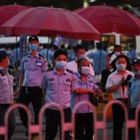 Police gather outside the Xinfadi meat wholesale market in Beijing on Friday. Throat swabs from 45 people have tested positive for the new coronavirus, an official said Saturday. | AFP-JIJI