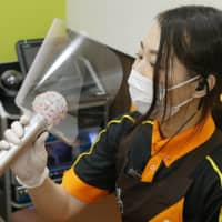 A worker holds a microphone that is covered with a plastic sheet to prevent COVID-19 infections at a karaoke parlor in Tokyo's Shinjuku Ward on Friday, as the store resumed operations following a coronavirus-necessitated closure. | KYODO