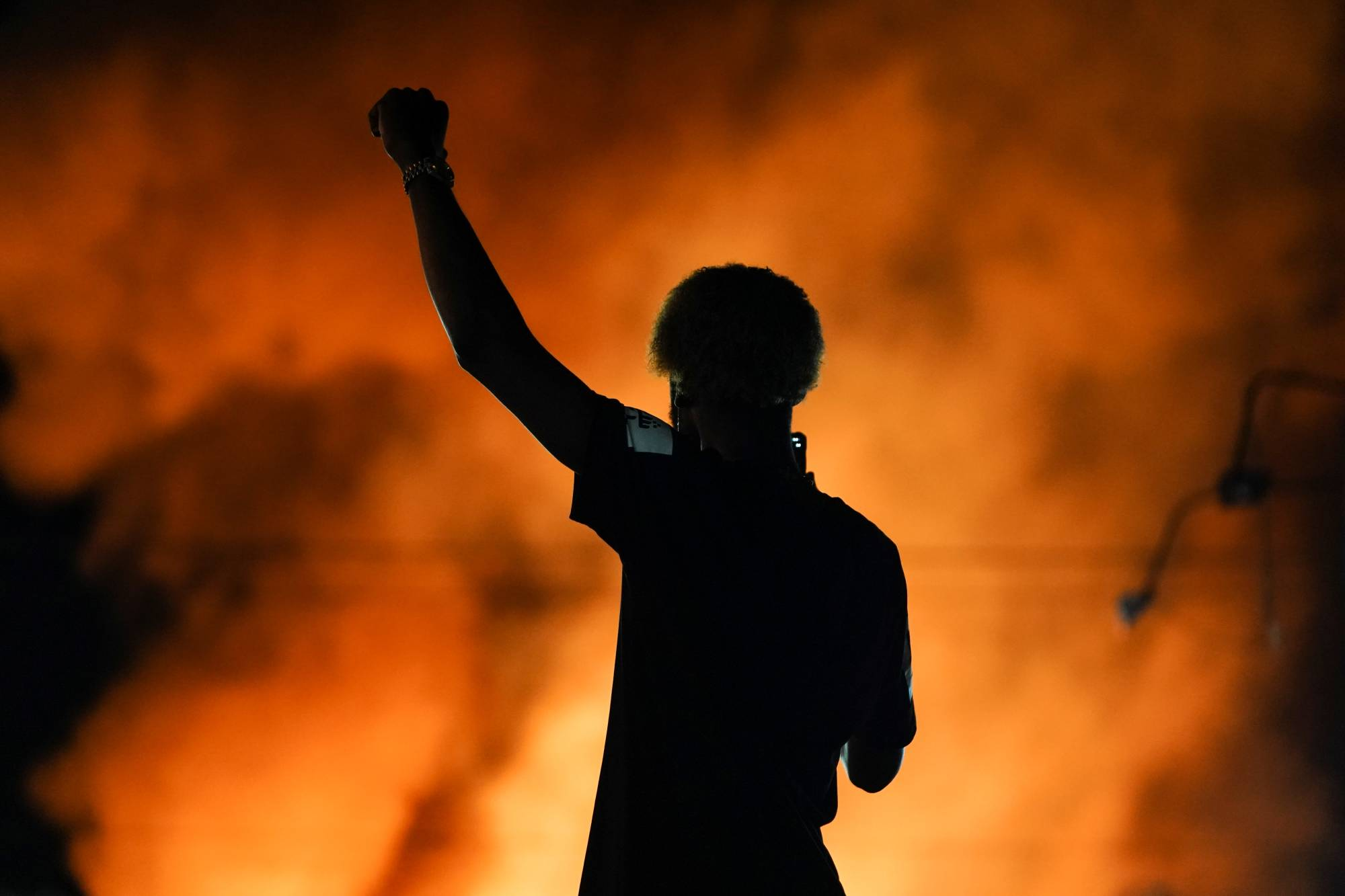 A protester watches as a Wendy's burns Saturday following the police shooting death of Rayshard Brooks in Atlanta.  | REUTERS