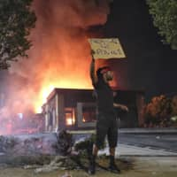 A person holds a sign as a Wendy's restaurant burns Saturday in Atlanta.  | ATLANTA JOURNAL-CONSTITUTION / VIA AP