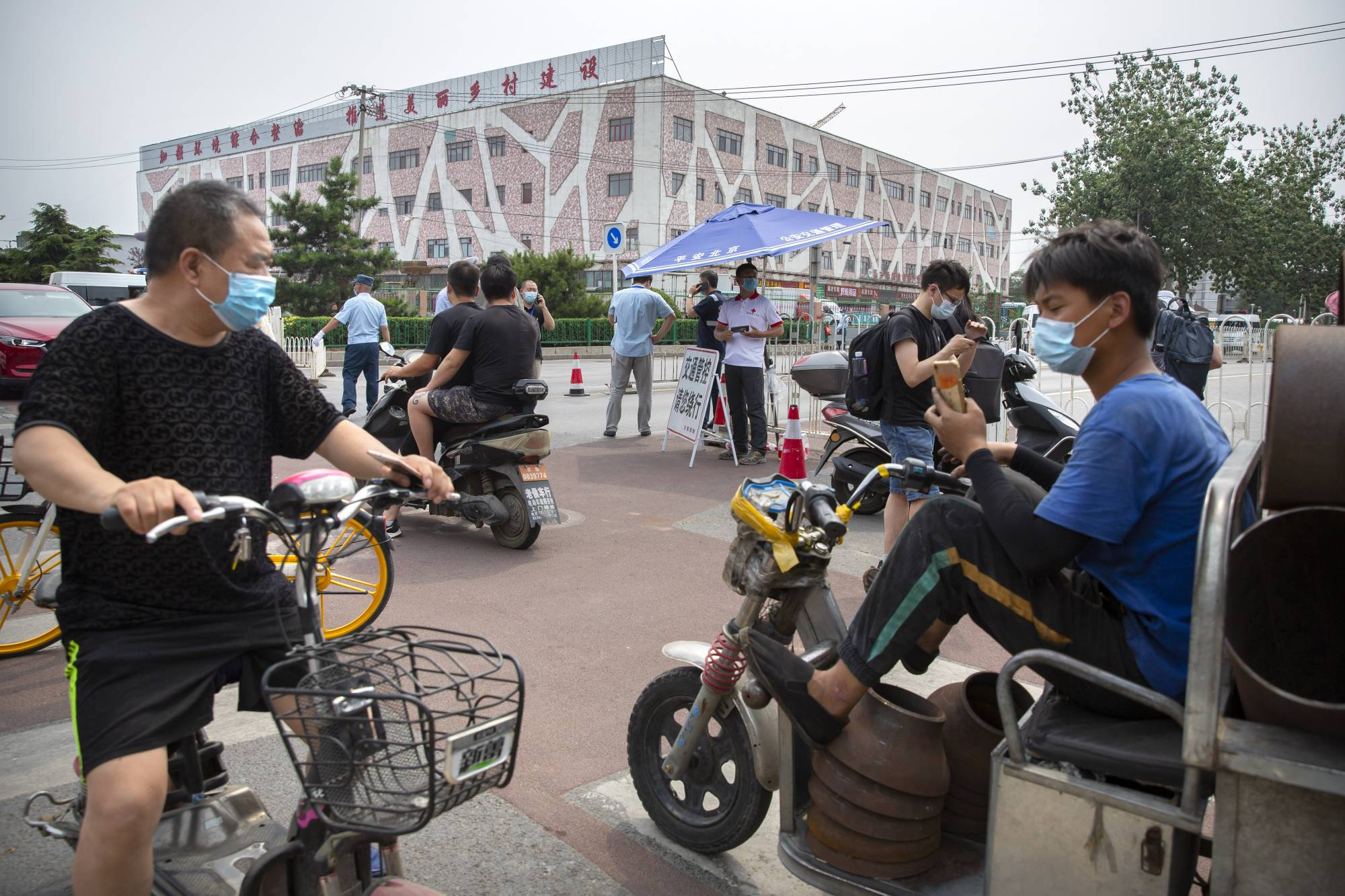 People stop at a checkpoint outside the Xinfadi wholesale food market district. Beijing closed the city's largest wholesale food market Saturday after the discovery of seven cases of the new coronavirus in the previous two days. | AP