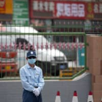 A security officer stands guard outside the Xinfadi wholesale food market district in Beijing on Saturday.  | AP