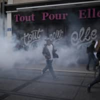 A protester reacts to tear gas fired by French riot police during a march against police brutality and racism in Marseille, France, on Saturday.  | AP