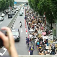 A long line of protesters make their way through the streets of Shibuya Ward on Sunday during a march organized by Black Lives Matter Tokyo. | RYUSEI TAKAHASHI