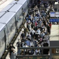 People get off the train at the Seoul Railway Station on Thursday. A resurgence of COVID-19 infections in the Seoul region is threatening the country's success story and prompting health authorities to warn that action must be taken now to stop a second wave.  | AP