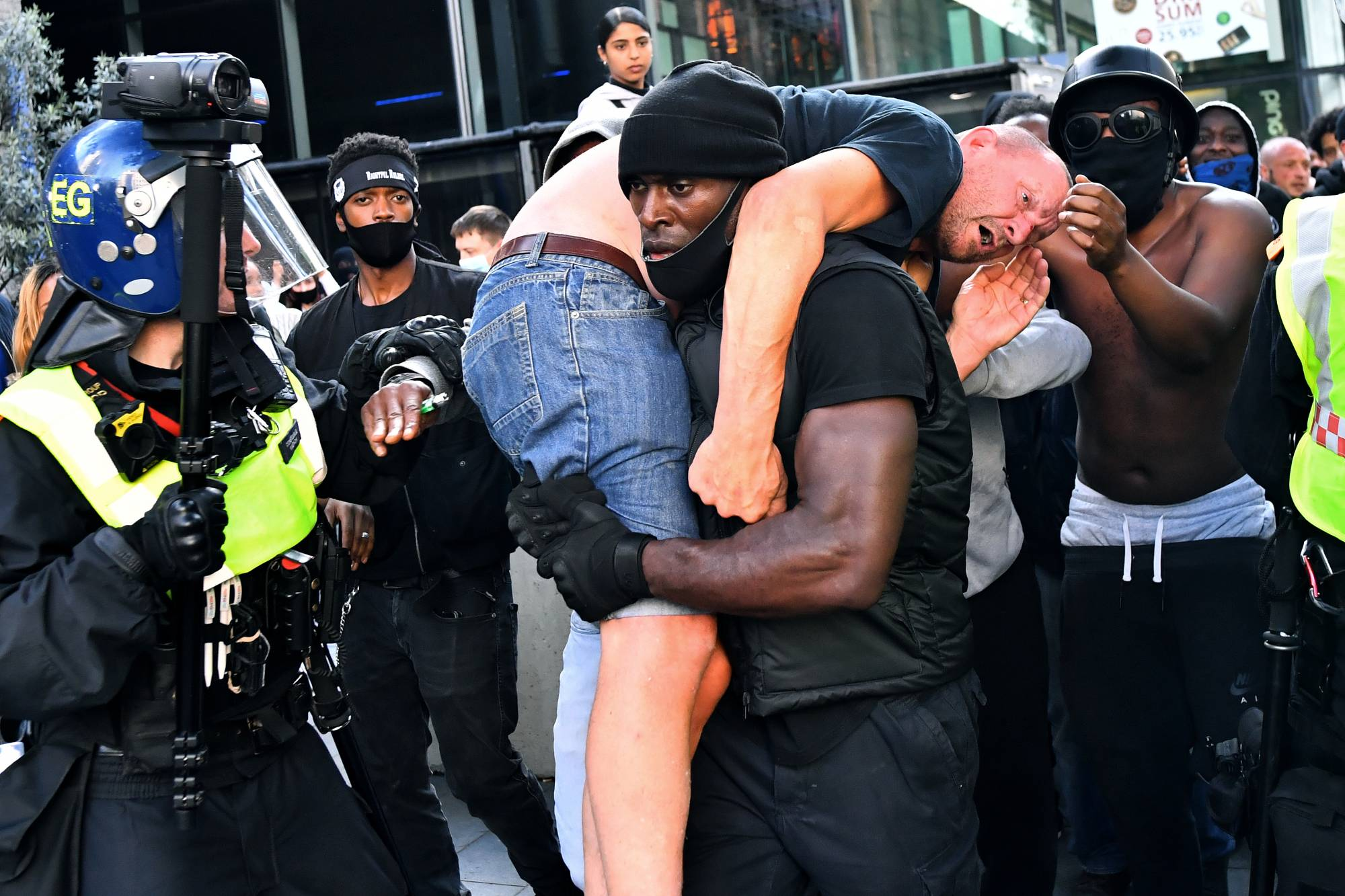 Patrick Hutchinson, a protester, carries an injured suspected far-right counterprotester to safety near Waterloo Station in London on Saturday during a Black Lives Matter protest following the death of George Floyd in Minneapolis police custody.  | REUTERS