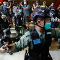 Riot police disperse pro-democracy demonstrators in Hong Kong on Friday.  | REUTERS