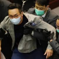 Alvin Yeung, a pro-democracy lawmaker, is removed by security officers during scuffles between pro-establishment and opposition lawmakers at the Legislative Council in Hong Kong on May 18. | BLOOMBERG