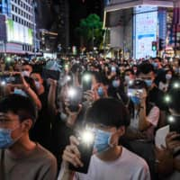 Pro-democracy activists hold up their phones as they sing during a rally in the Causeway Bay district of Hong Kong on Friday. Thousands sang a protest anthem and chanted slogans across the city as they marked the one-year anniversary of major clashes between police and pro-democracy demonstrators.  | AFP-JIJI