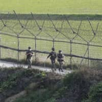 South Korean soldiers patrol along a fence in Paju, South Korea, on Monday near the border with North Korea. | AP