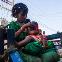 A girl holds a baby at the Aung Mingalar quarter for Rohingya Muslims in Sittwe in Myanmar's Rakhine state last month.  | AFP-JIJI
