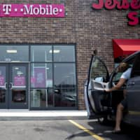 A person exits a vehicle in front of a T-Mobile U.S. Inc. store in Peru, Illinois, last July. SoftBank Group Corp. said it is considering the sale of its T-Mobile U.S. Inc. shares. | BLOOMBERG