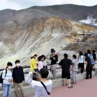 Tourists take photos in Hakone, Kanagawa Prefecture, on May 30, as Japan slowly reopens tourism and other businesses after lifting its state of emergency earlier in the month. | KYODO