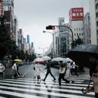 Pedestrians cross a street in the Shinjuku district of Tokyo on Sunday. | BLOOMBERG