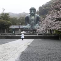 A woman visits the Kotokuin Temple in Kamakura, Kanagawa Prefecture, in April. The government has restarted the application process for back-office work for its Go To Campaign tourism promotion project. | AP