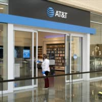A worker wearing a protective mask disinfects the doors of an AT&T Inc. store in Dallas, Texas, on May 1. | BLOOMBERG