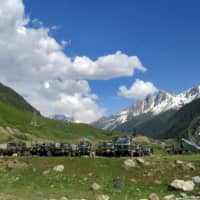 Indian Army soldiers walk past their parked trucks at a makeshift transit camp before heading to Ladakh, near Baltal on Tuesday.  | REUTERS
