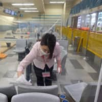 An employee disinfects seats at a bowling center in Tachikawa in western Tokyo on May 27. | AFP-JIJI