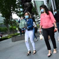People with protective masks walk with take away food at the Raffles Place financial business district in Singapore on Monday. | AFP-JIJI