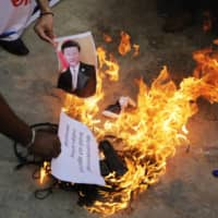 An Indian man burns a photograph of Chinese President Xi Jinping during a protest in Ahmedabad, India, on Tuesday. | AP