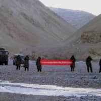Chinese troops hold a banner reading 'You've crossed the border, please go back' in Ladakh, India, in 2013.  | AP