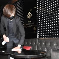 An employee at Cruise, a host club in the Kabukicho district of Tokyo, disinfects tables and walls hours before the arrival of customers on Friday. | TOMOHIRO OSAKI