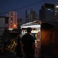 People buy food from a street vendor near a subway exit in Beijing on June 10. | AFP-JIJI