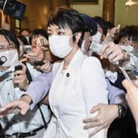Anri Kawai is surrounded by reporters in the Diet after the Upper House plenary session Wednesday. | KYODO