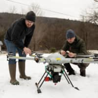 Timothy De Smet and Alex Nikulin prepare a Ukrainian Multirotor Technologies  Cicada-M drone to fly with a magnetometer to detect abandoned oil wells in Olean, New York. | REUTERS