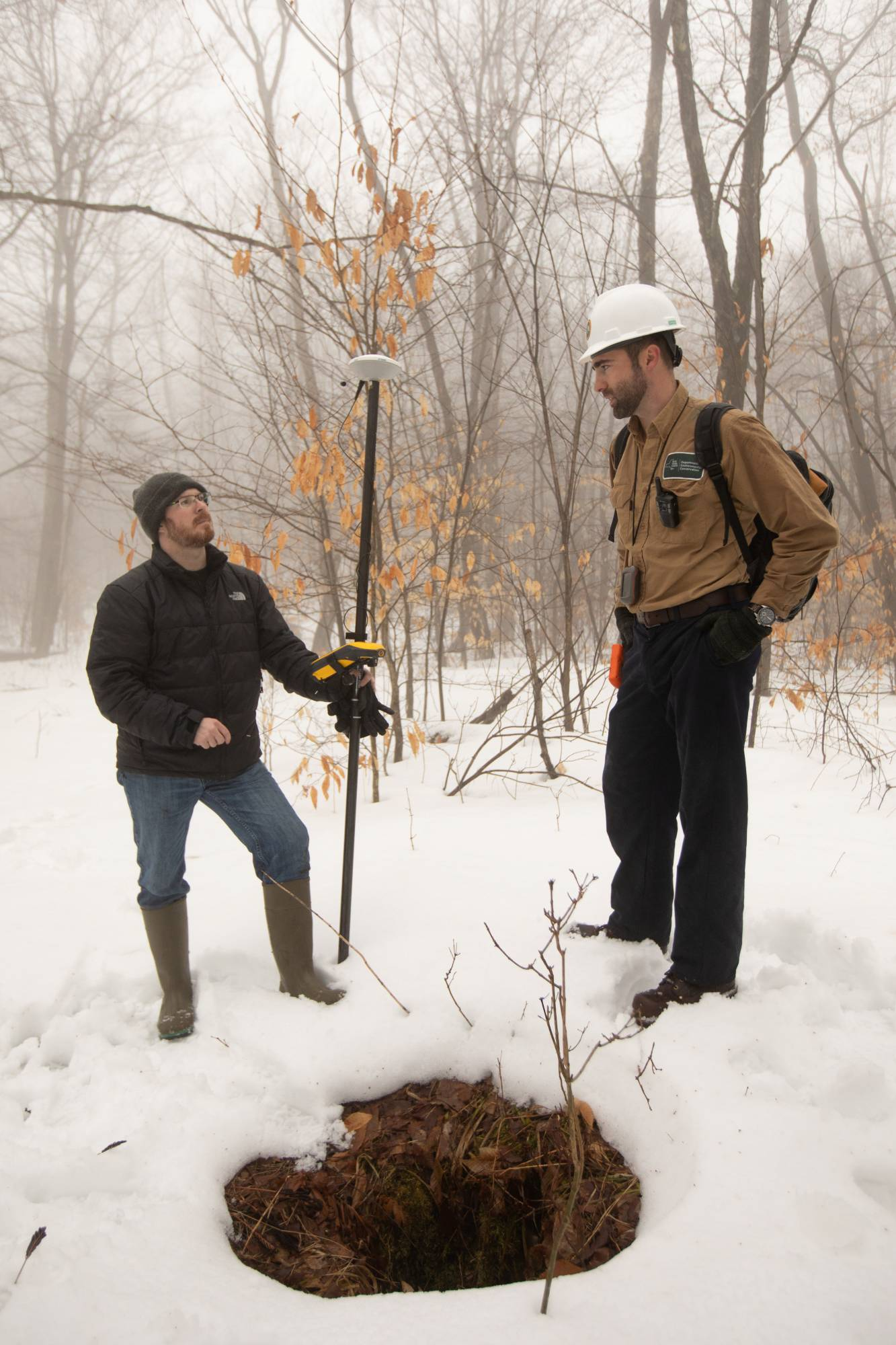 Timothy De Smet and Nathan Graber use a global navigation satellite system and geodetic antenna to locate an abandoned oil well in Olean, New York. | REUTERS