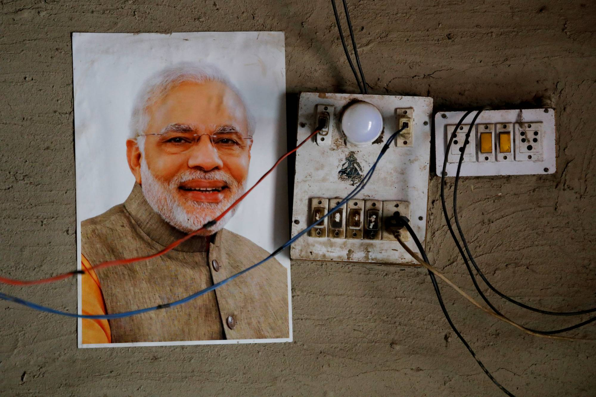 A picture of Narendra Modi, India's Prime Minister, is posted on a wall at the home of a family who are refugees from Pakistan, at a Hindu refugee settlement near Majnu ka Tilla in New Delhi. | REUTERS