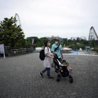 A family visits the newly reopened Yomiuriland amusement park in Tokyo on Tuesday. | AP