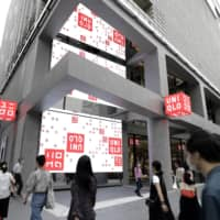 Pedestrians walk past Uniqlo Tokyo ahead of the store's grand opening the following day. | BLOOMBERG