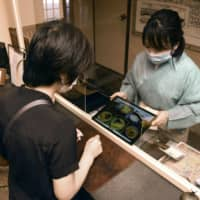 A waitress of a traditional Japanese-style inn attends to a guest through a small hole in a plastic panel installed at its front desk in the Arima hot spring resort in Kobe on June 4 to prevent coronavirus infection. | KYODO